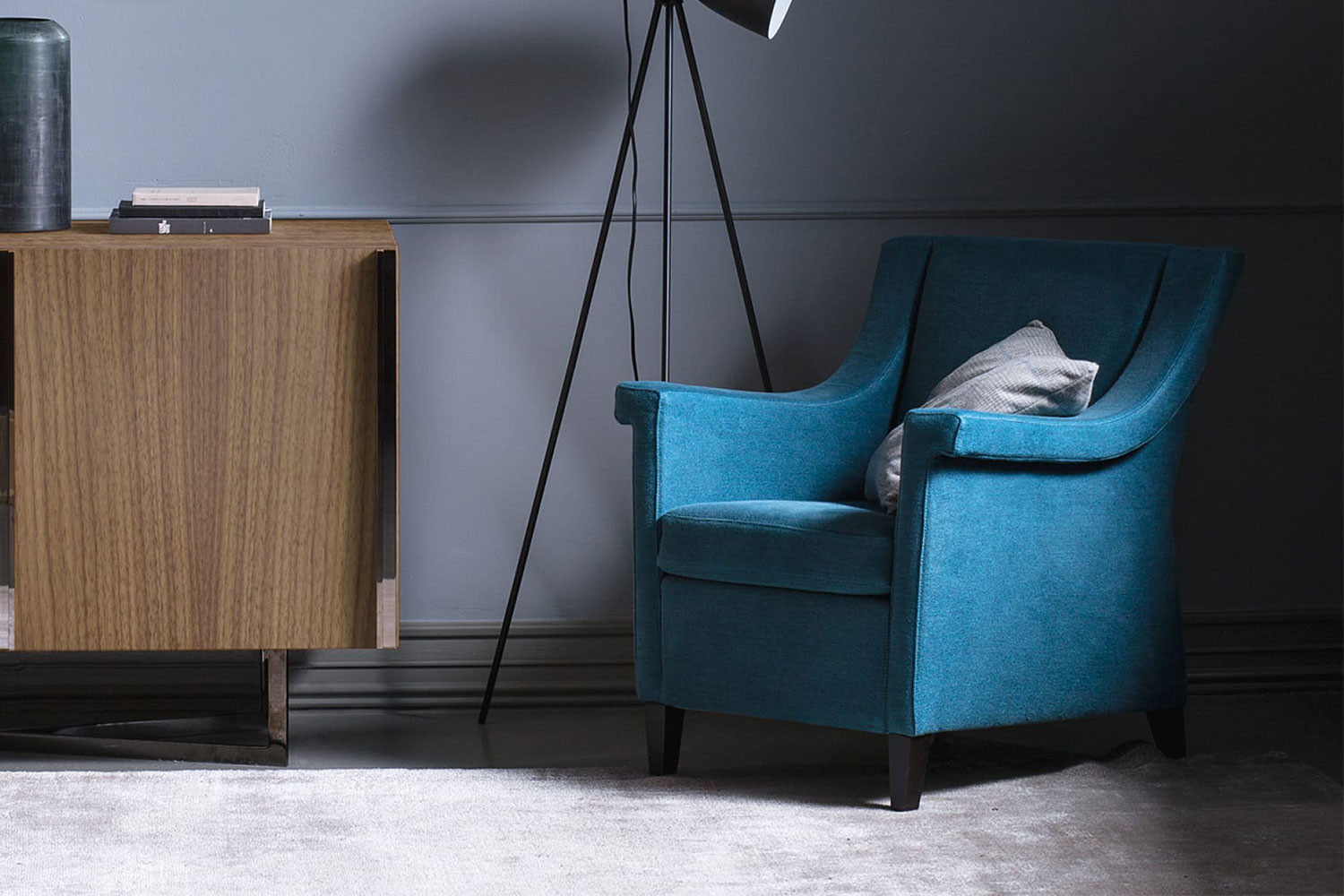 Narrow armchair with slope arms and high wooden legs