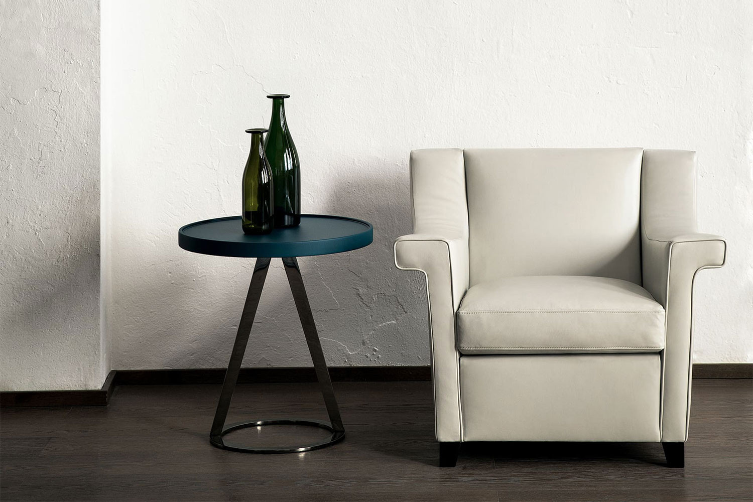 Modern slope-arm club chair with a low back, hardwood square tapered legs and distinctive winged arms