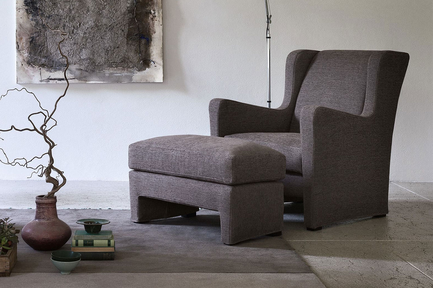 Modern wingback armchair with footstool, comfortable high back and sloping arms