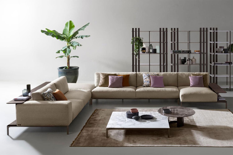 Contemporary high legged modular sofa with wrap around bookcase and aluminium raised deck