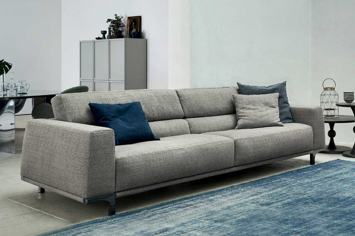 Contemporary low-back sofa with l-shaped tall legs, wide arms and ergonomic backrest