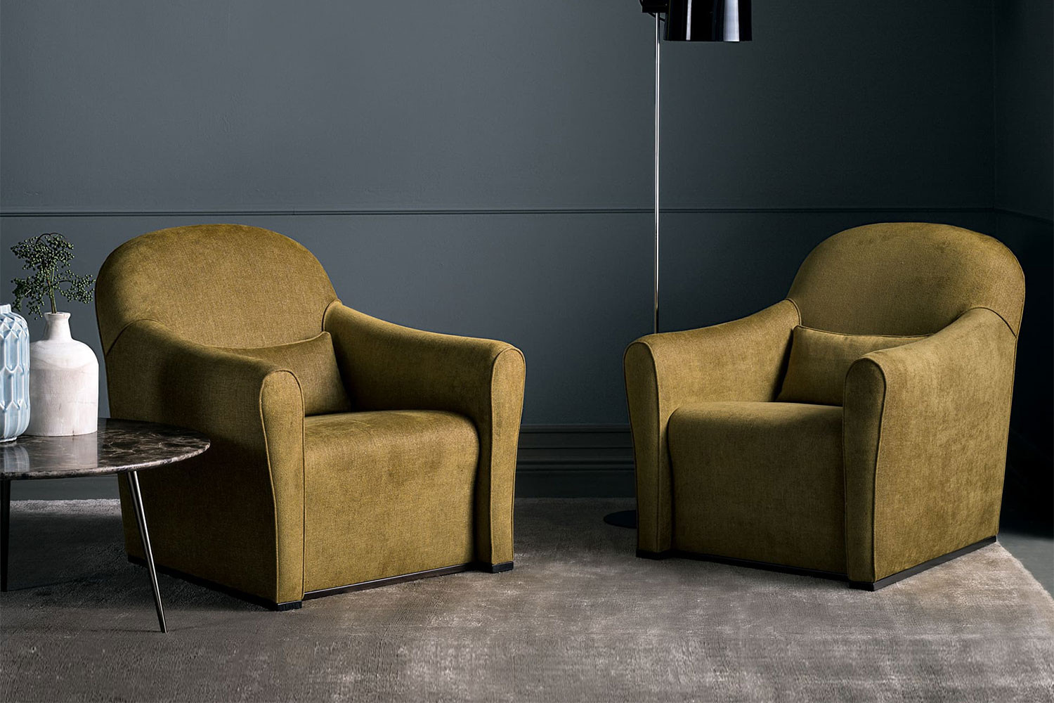 Modern round back club chair with curved flared arms and fixed seat cushion