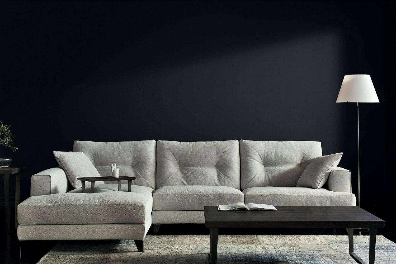 Gemütliches Sofa mit hoher Rückenlehne, Kissen mit Ziernähten und hohen Metall- oder Holzfüßen