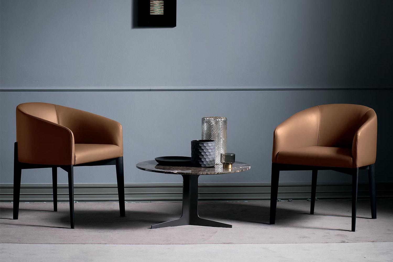 Moderner Polsterstuhl mit umlaufenden Armlehnen und schwarz matt lackierten Massivholzbeinen
